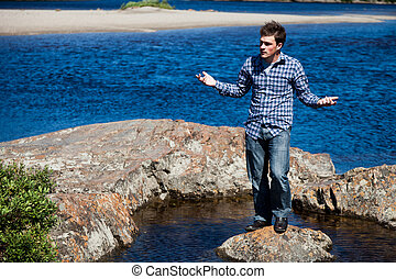 Young man lost on a rock in the middle of the water