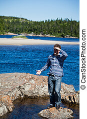 Young man stands on a rock in the middle of nowhere