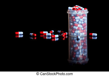 Container full of pills isolated on black background