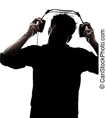 Male in silhouette putting headphones