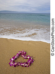 Purple orchid lei on beach