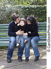 Asian mother caucasian father and child on a parkbench - A...