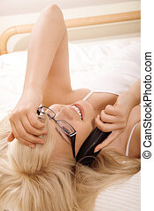 Young woman talking on phone in bed