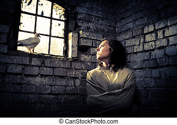 Woman and white dove in prison as a symbol of dreams of...