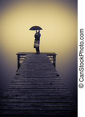Lonely woman protected by an umbrella on bridge