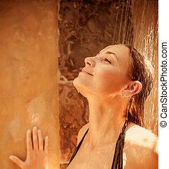 Pretty woman taking shower outdoors, enjoying fresh falling...