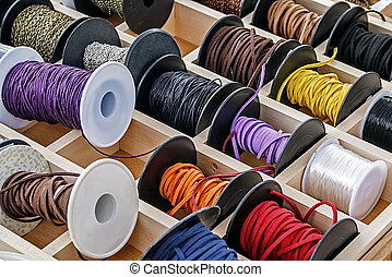 Spools with chains and colored ribbons for made trinkets.