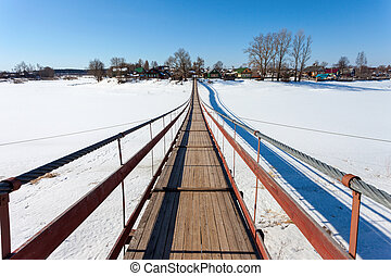 Suspension foot bridge over the frozen river