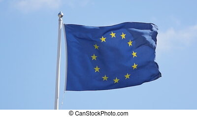 European flag in strong wind stormy situation, against a...