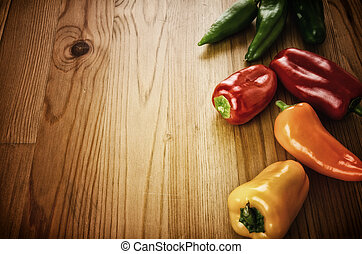 Peppers on wooden background - Decorative border with...