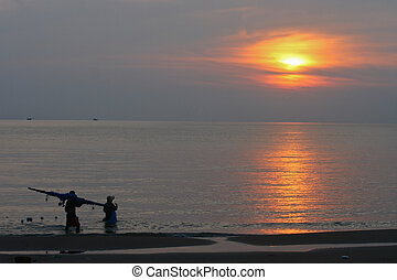 Sunset on the beach with fishermen