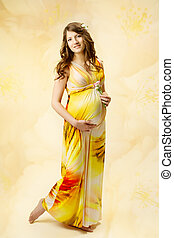Pregnant woman in long dress over yellow art background.