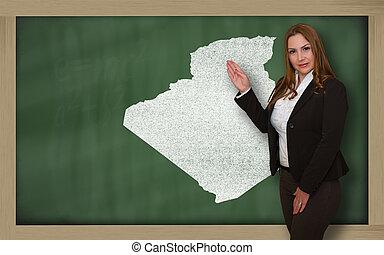 Teacher showing map of algeria on blackboard