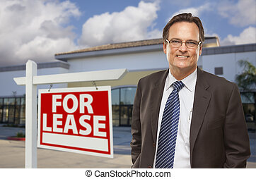 Businessman In Front of Office Building and For Lease Sign