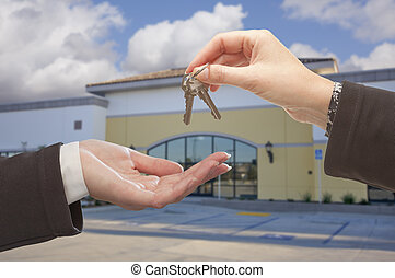 Agent Handing Over the Keys in Front of Business Office -...