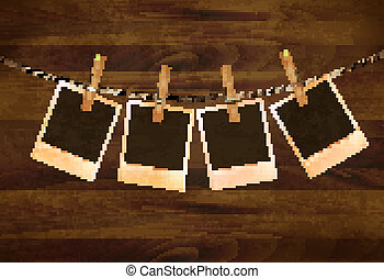 Retro photos hanging on a rope on dark wooden background....