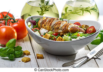 Closeup of healthy salad with chicken, tomato and olive