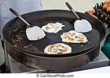 Oysters fried in egg batter being cooked in a pan