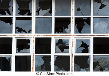 Broken windows of old building. White frames