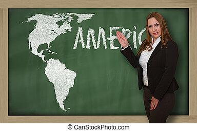 Teacher showing map of america on blackboard