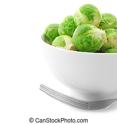 Brussel sprouts in bowl and fork on white background
