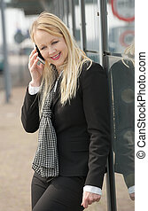 Portrait of a business woman talking on the phone outside