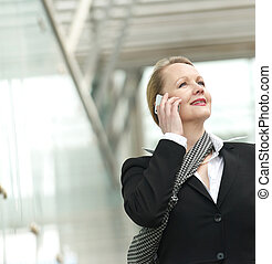 Portrait of a business woman talking on the phone outdoors