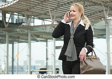 Portrait of a traveling business woman talking on mobile phone outdoors