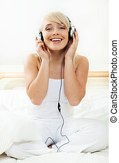 Young woman listening to the music on the bed