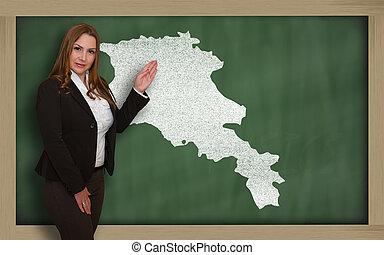 Teacher showing map of armenia on blackboard