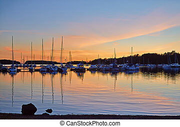 Yachting port in over sunset with row of sailboats Quiet...