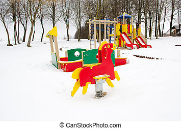 empty colorful playground surrounded snow winter - empty...