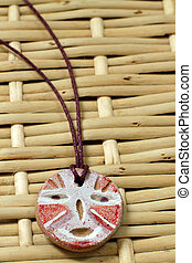 clay african amulet with mask red and white