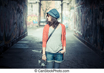 Beautiful stylish woman listening to music in the street