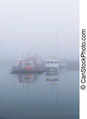 Fishing vessels in a foggy misty morning at Harbor