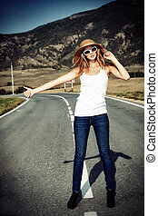 blonde hitchhiker - Beautiful young woman posing on a road...