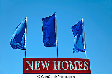 New Homes Sign - Red New Homes Sign with Blue Flags Waving