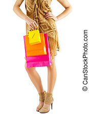 close up view on female legs and paper bags in hand