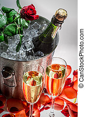 Closeup of red rose and cold champagne for celebration