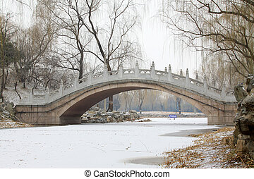 Stone arch bridge building landscape in winter in Old summer...