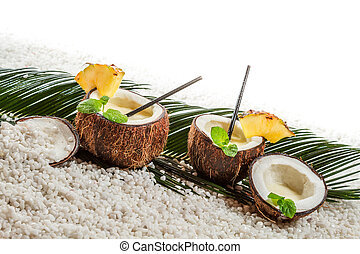 Few pinacolada drinks in coconut on white beach
