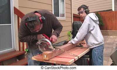Man and boy sawing a board