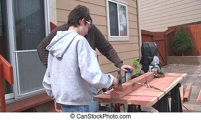 Man and boy cutting wood