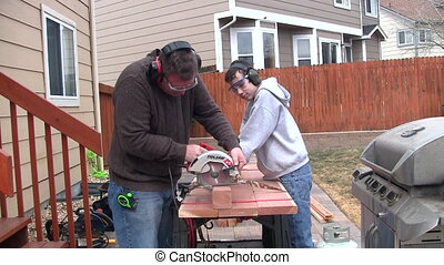 Man and boy sawing