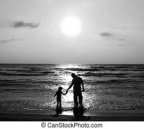 father and son on a walk by the sea at sunset Black and...