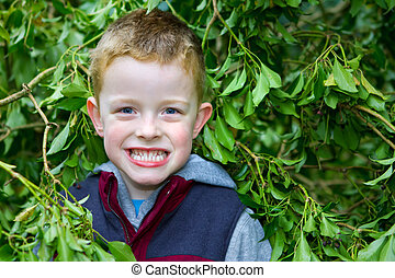 happy little boy smiling through the leaves