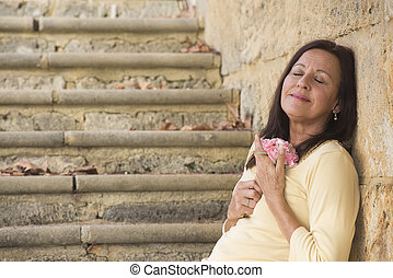 Happy mature woman in love with rose