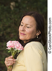 Mature Woman in love with rose - Portrait attractive mature...