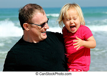 Portrait of father and daughter on the beach