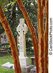 Cross Beyond Crepe Myrtle Tree - A white stone cross on a...